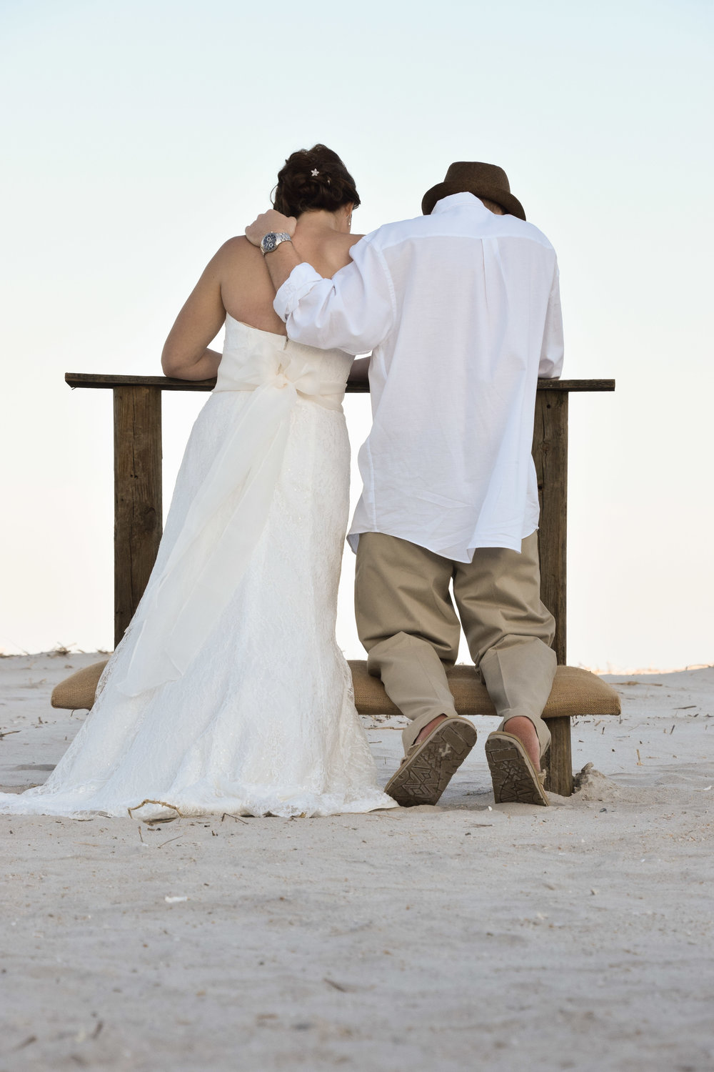 Bride and groom kneeling on the beach.