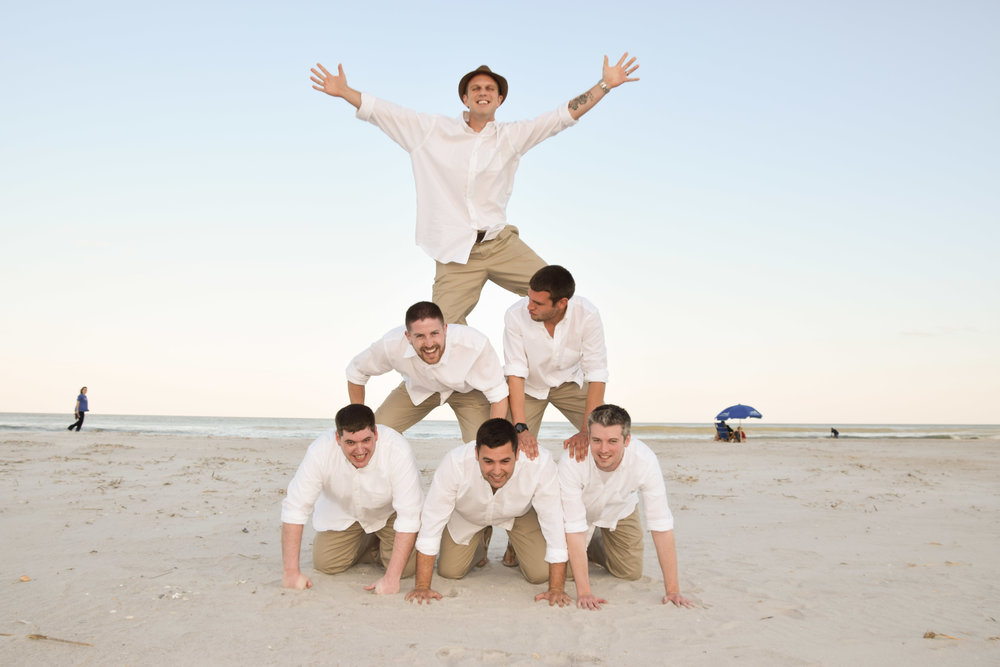 Groom and groomsmen make a pyramid on the beach.