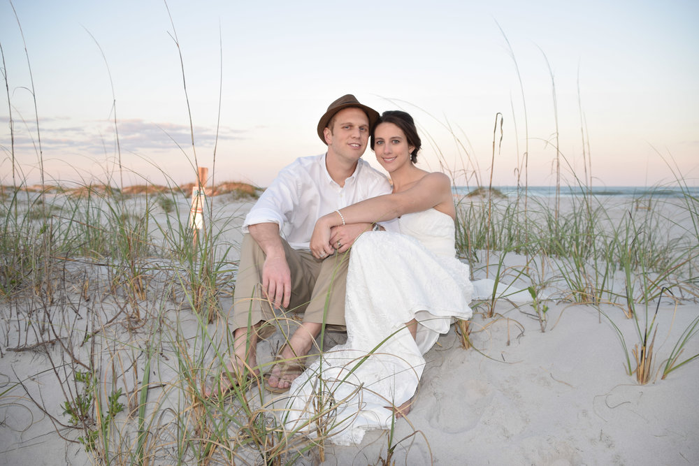 Bride and Groom sitting on the dunes looking at the camera.