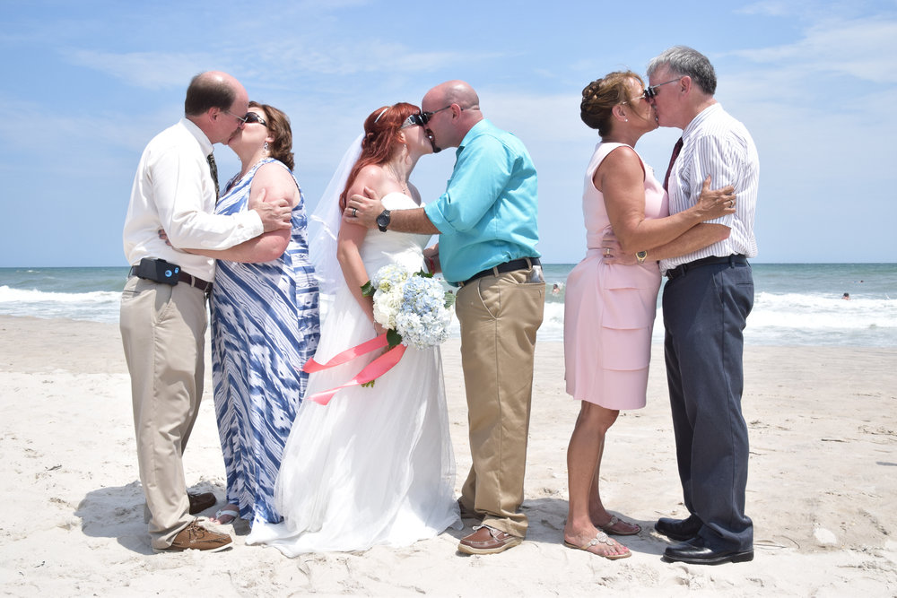 Bride and Groom and parents all kissing on the beach.