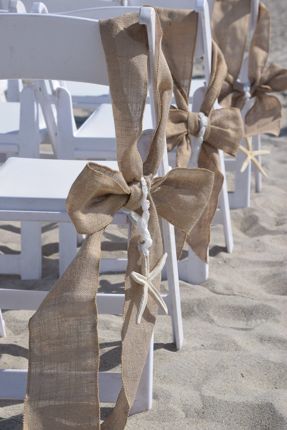 Burlap and starfish chair decorations. Beach Wedding.