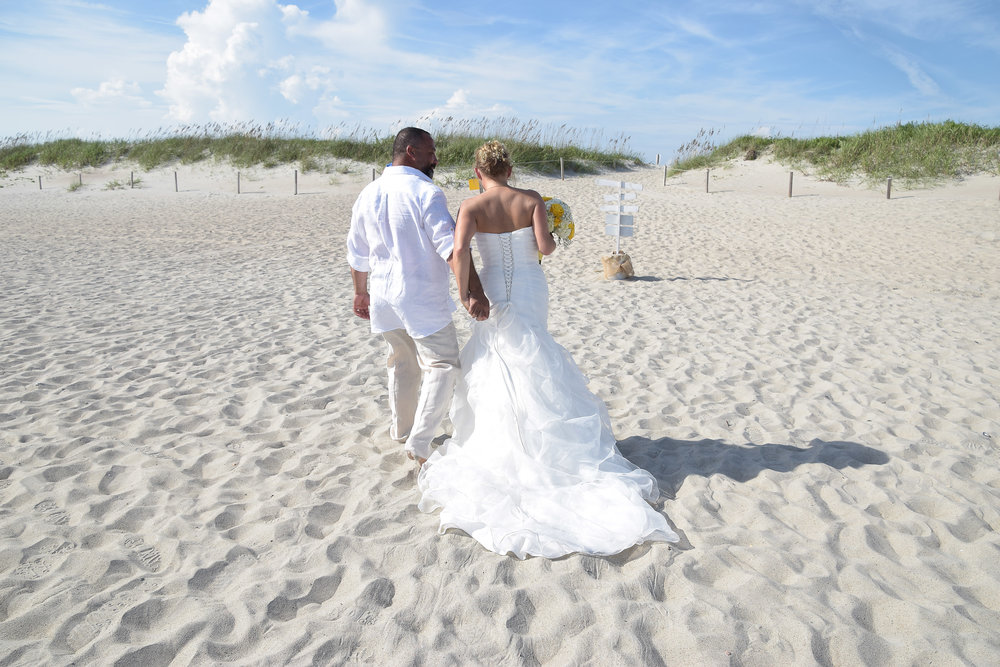 Couple walking on the beach after ceremony.