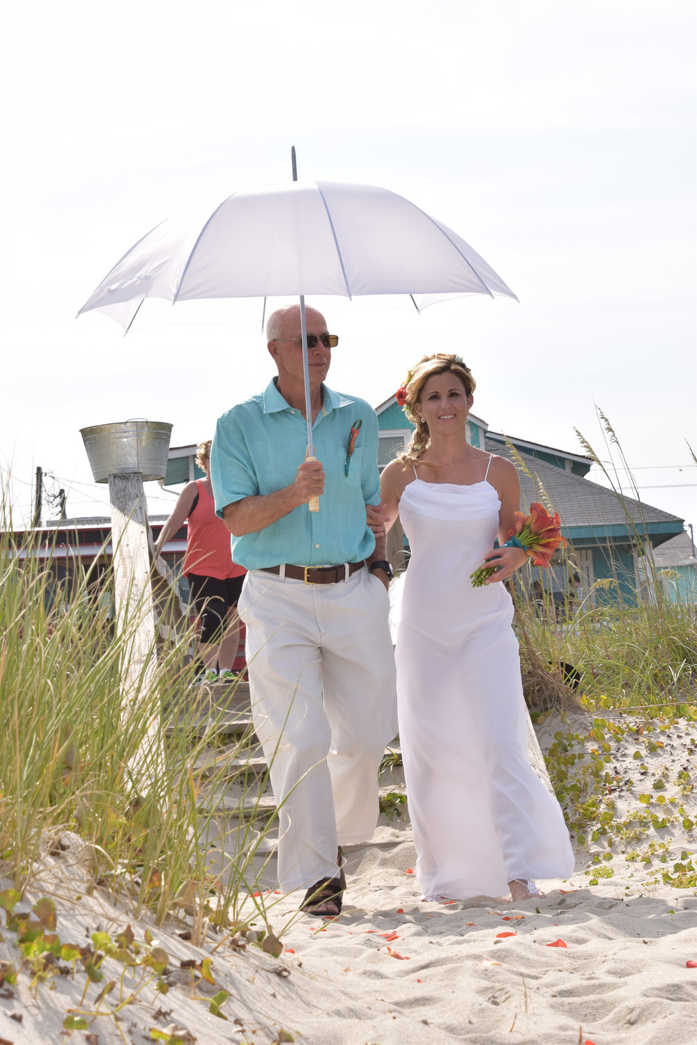 Dad walking his daughter to the alter at beach wedding.