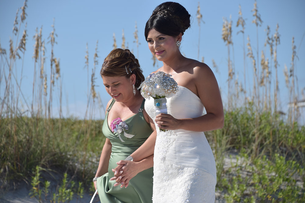 Brides walks to beach ceremony.