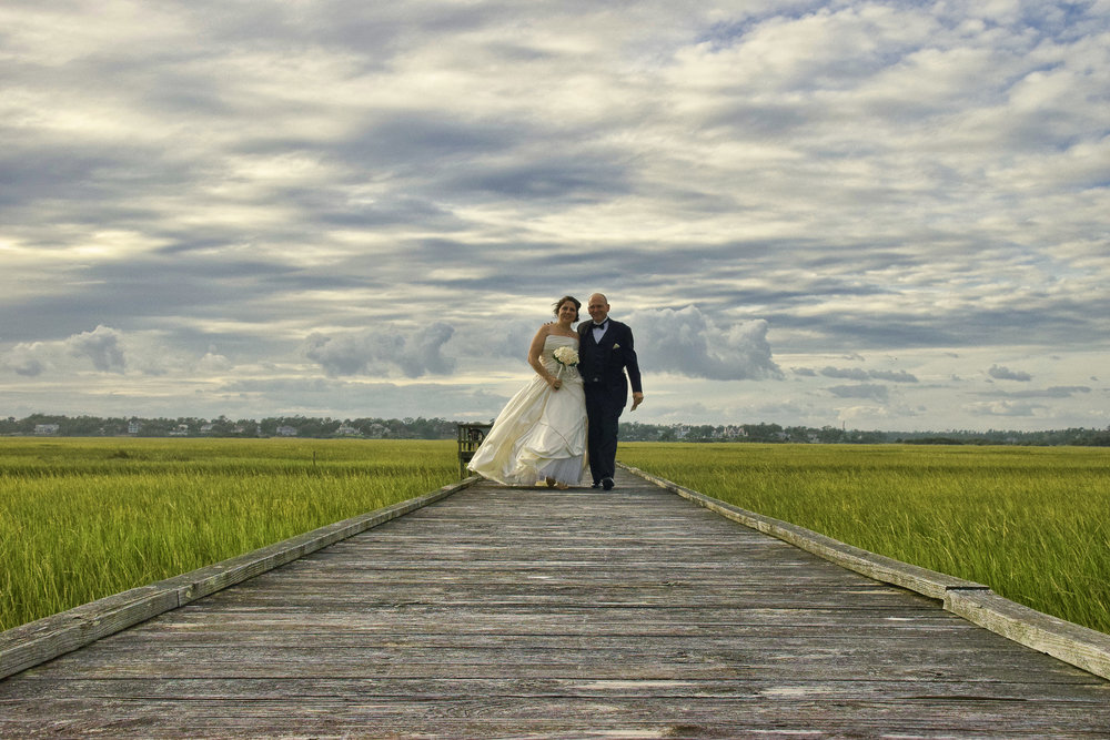 Bride and groom on boardwalk.