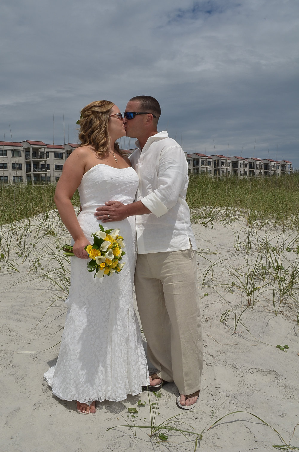 Bride and groom kissing on the beach.