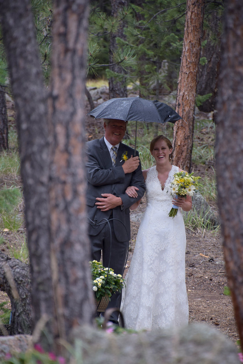 Dad walking bride to altar with umbrella.