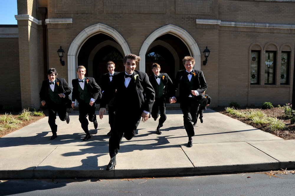 Groom and groomsmen running.