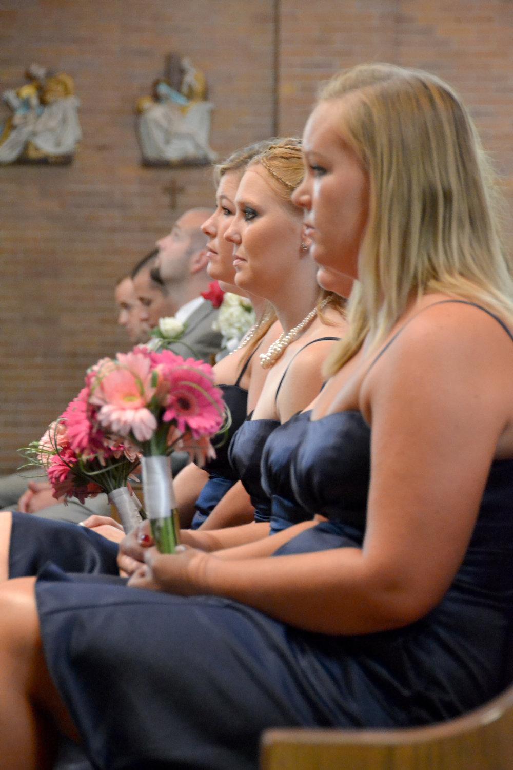 Candid shot of bridesmaids during church ceremony.
