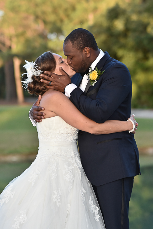 Bride and groom kiss at Porters Neck Country Club.
