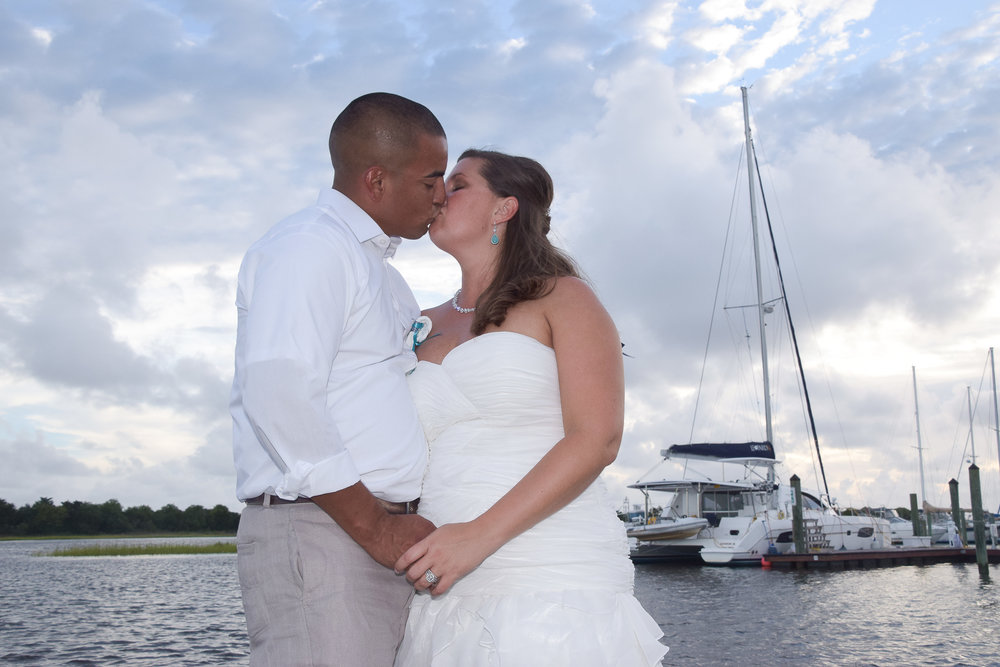 Bride and groom sharing a kiss at the Southport Marina.
