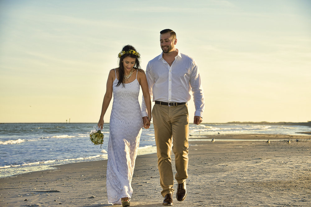 - Candid shot of bride and groom walking on Wrightsville Beach, NC after the ceremony.