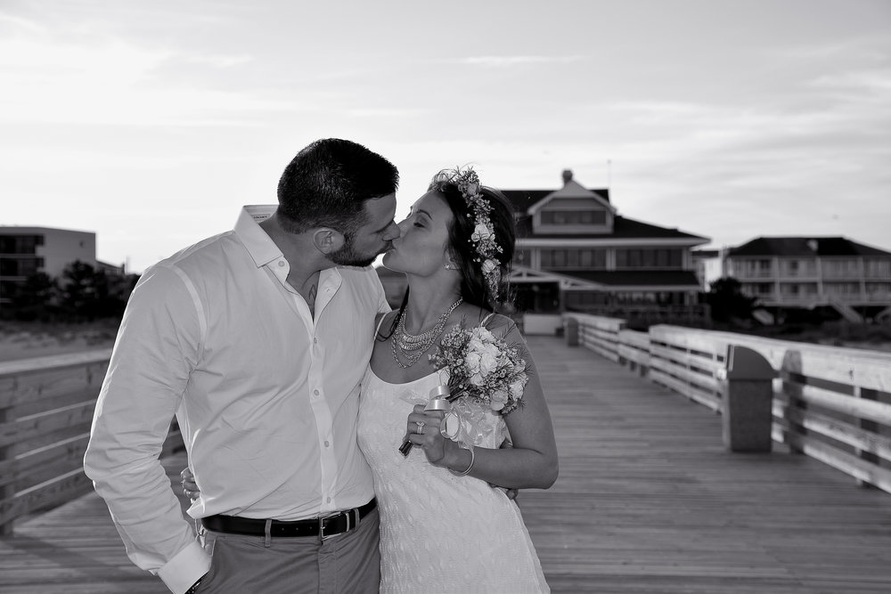 - Monochrome image of bride and groom sharing a kiss with the Oceanic Restaurant in the background. Wrightsville Beach, NC.