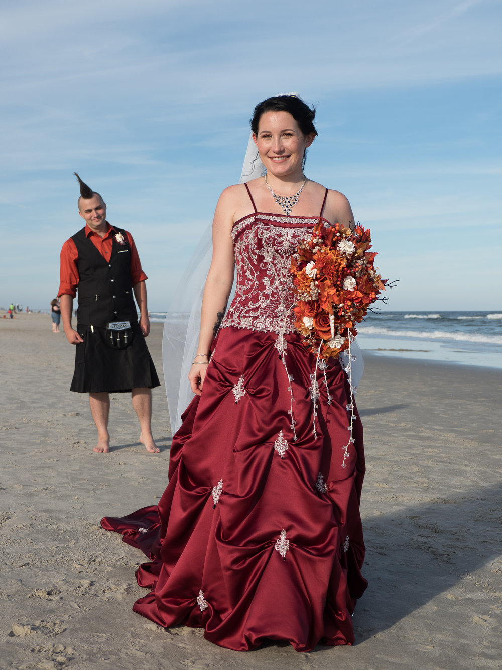 Red - A very beautiful bride in very non-traditional dress at a beach wedding with her equally non-traditional husband in the back. Carolina Beach, NC.