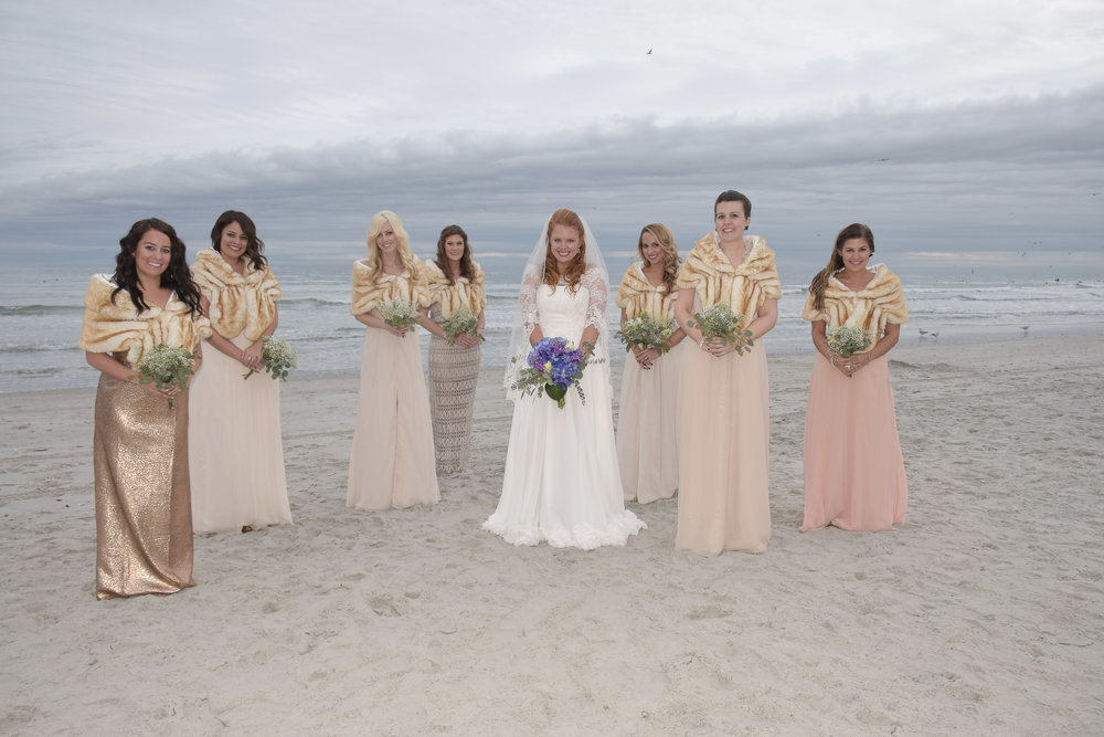 - Bride and bridesmaids on a cold January Beach, ocean in the background. Wrightsville Beach, NC.