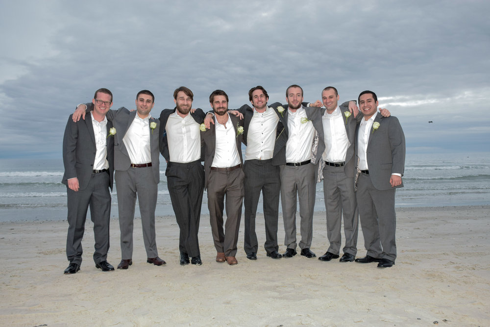 - Groom and groomsmen casual pose on a January beach. Wrightsville Beach, NC.