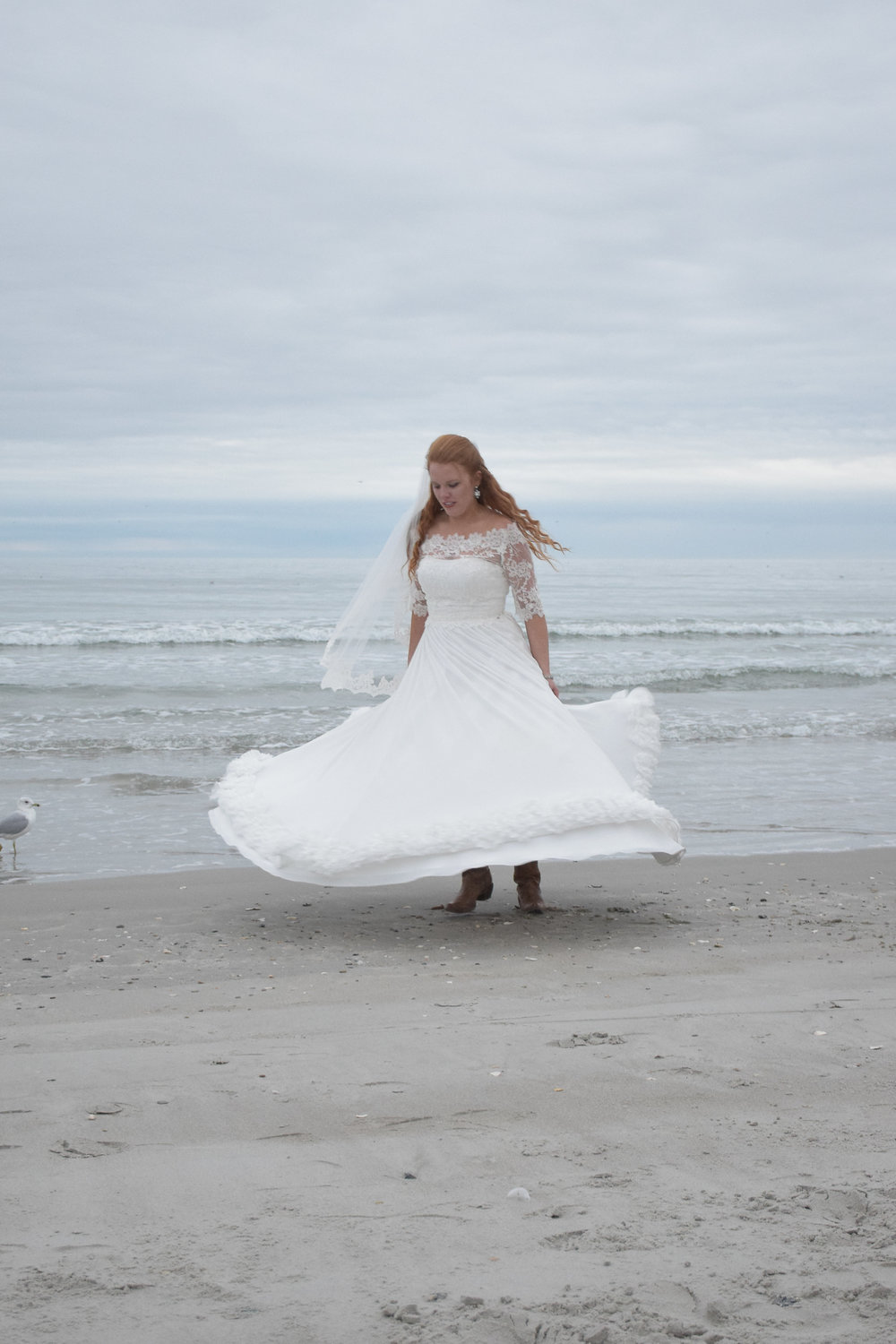- Bride flaring her dress on a cold January Beach. Wrightsville Beach, NC.