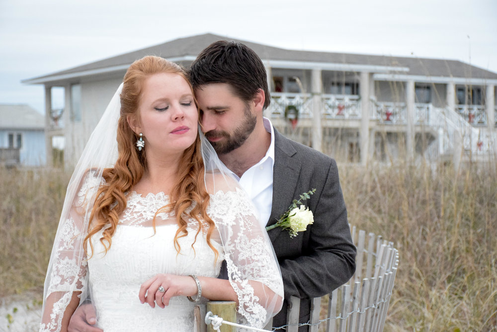 - Candid moment between bride and groom with beach house in the background. Wrightsville Beach, NC.