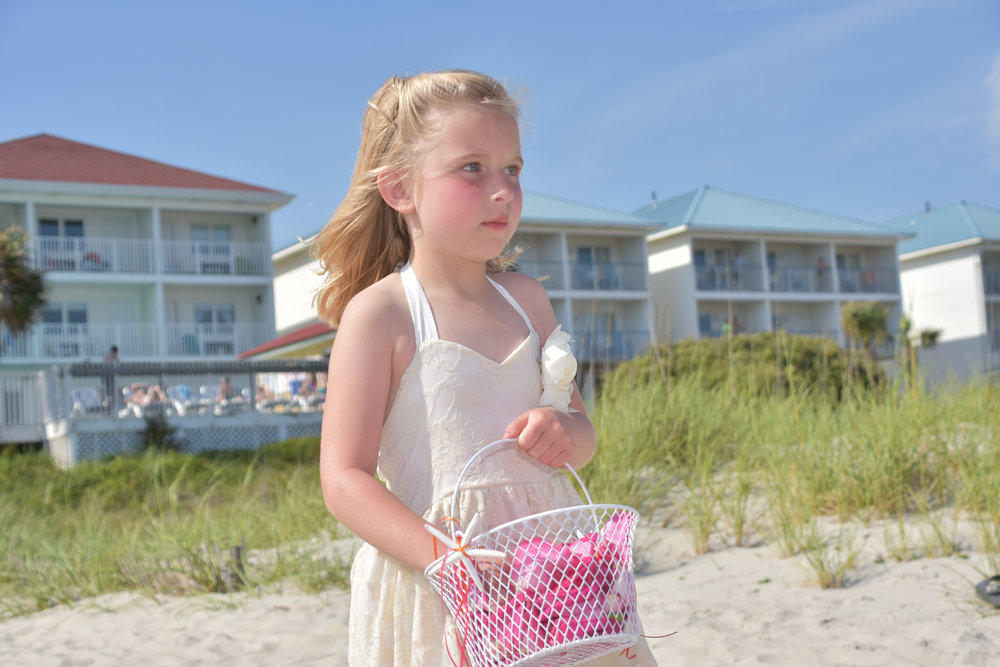 - Flower girl walking down the beach with basket  in hand on Ocean Isle Beach, NC.