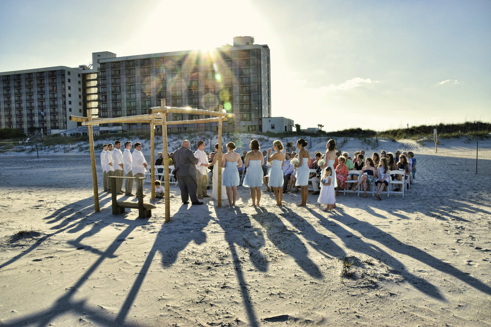 - Beach Wedding Ceremony on Wrightsville Beach at Shell Island Resort. Shell Island Resort in background with sun peaking over roofline. . Billy Beach Photography.
