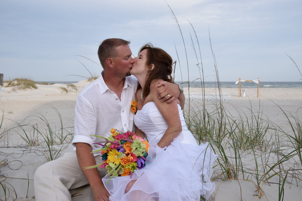 - Bride and Groom sharing a kiss after their wedding on Wrightsville Beach, NC. Sitting near dune with wedding arbor and beach in the background. Billy Beach Photography.