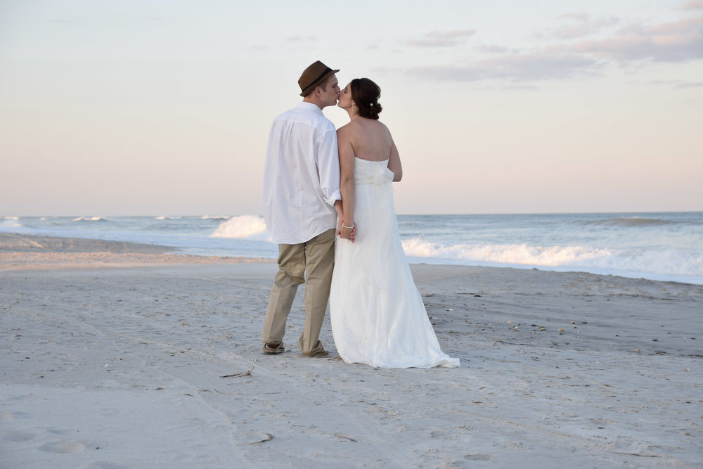 - Bride and groom sharing a kiss with their backs to the camera at Shell Island Resort in Wrightsville Beach, NC. Ocean in the background. Billy Beach Photography.