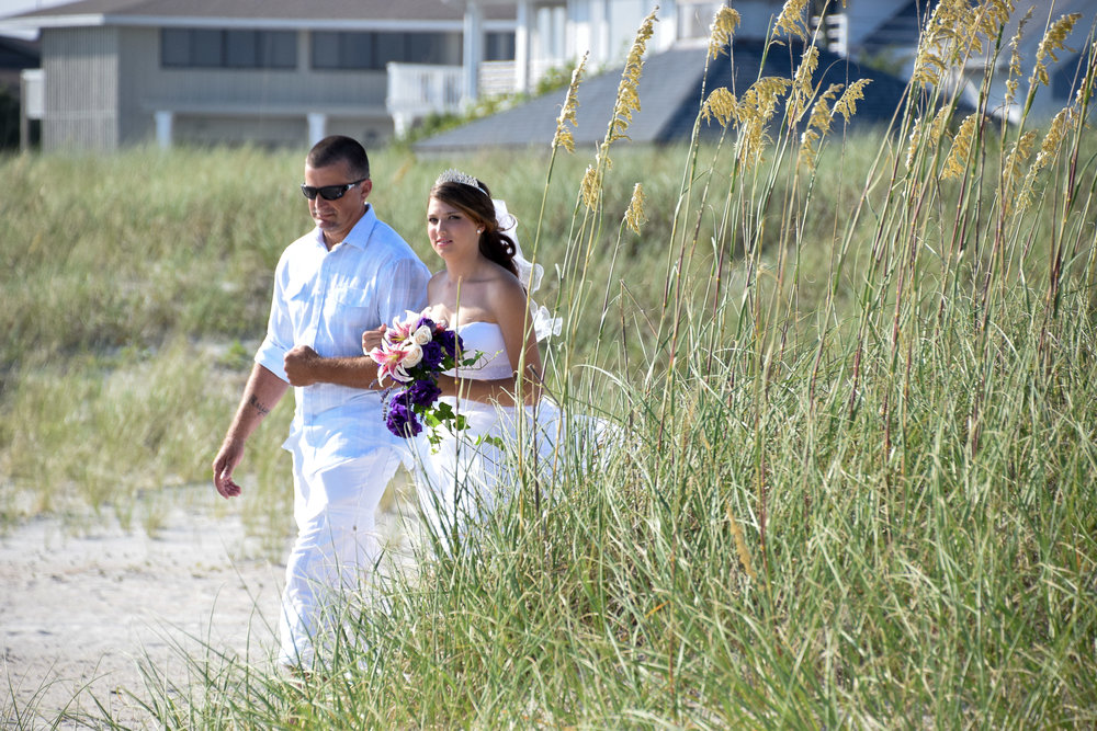 - Bride being escorted by her father to her wedding ceremony at access #43 in Wrightsville Beach, NC. Sea Oats in the fore ground and beach houses in the background. Billy Beach Photography.