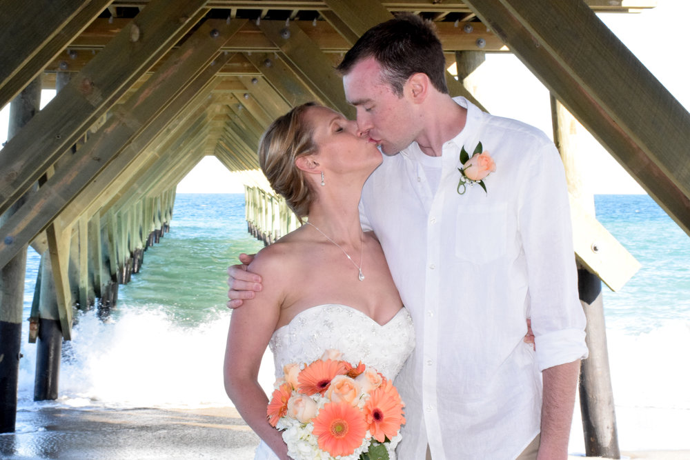 - Bride and groom sharing a kiss under the Oceanic Pier in Wrightsville Beach, NC. Ocean in the background. Billy Beach Photography.