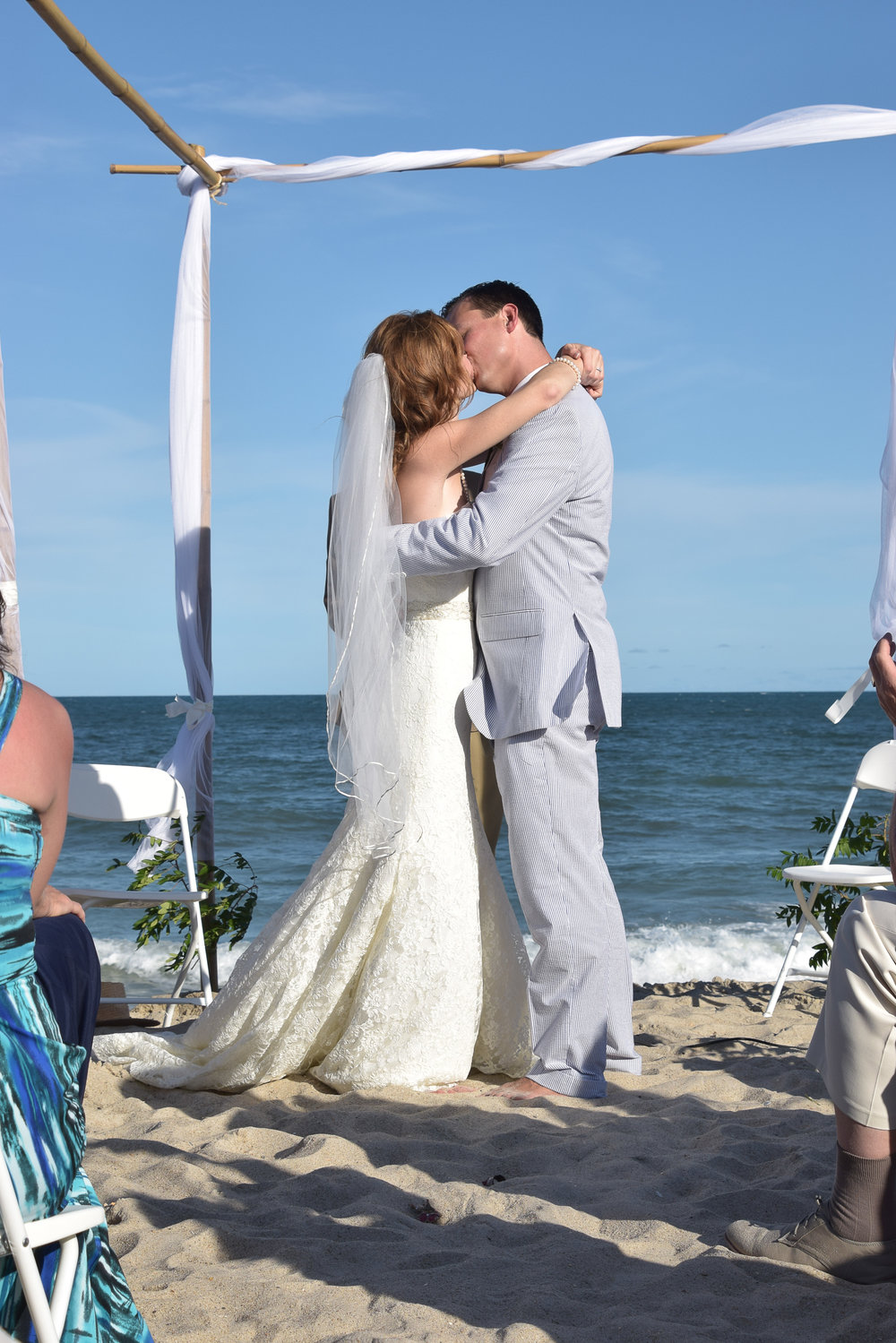 - First kiss at their wedding ceremony on Carolina Beach, NC. Under bamboo arbor with ocean in the background. Billy Beach Photography.