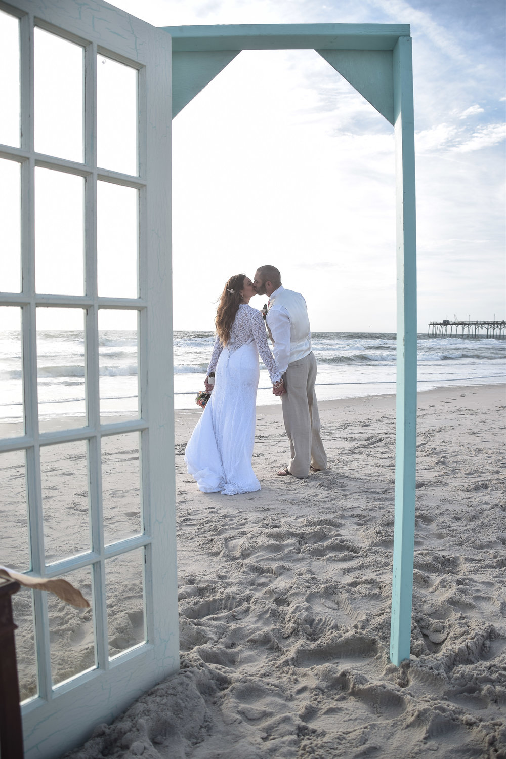 - A kiss through a prop door, on Carolina Beach, NC. Ocean and pier in the background. North End of the beach. Billy Beach Photography.