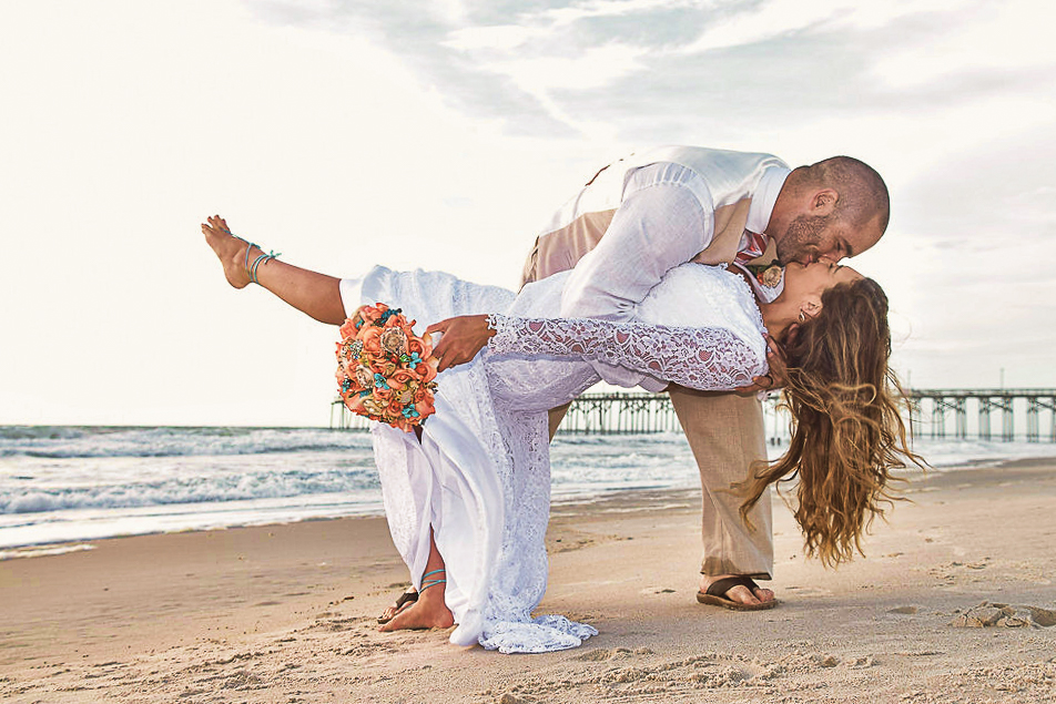 - Groom dips as bride while she is holding bouquet with the pier and ocean in the background. North end of Carolina Beach, NC. Billy Beach Photography.