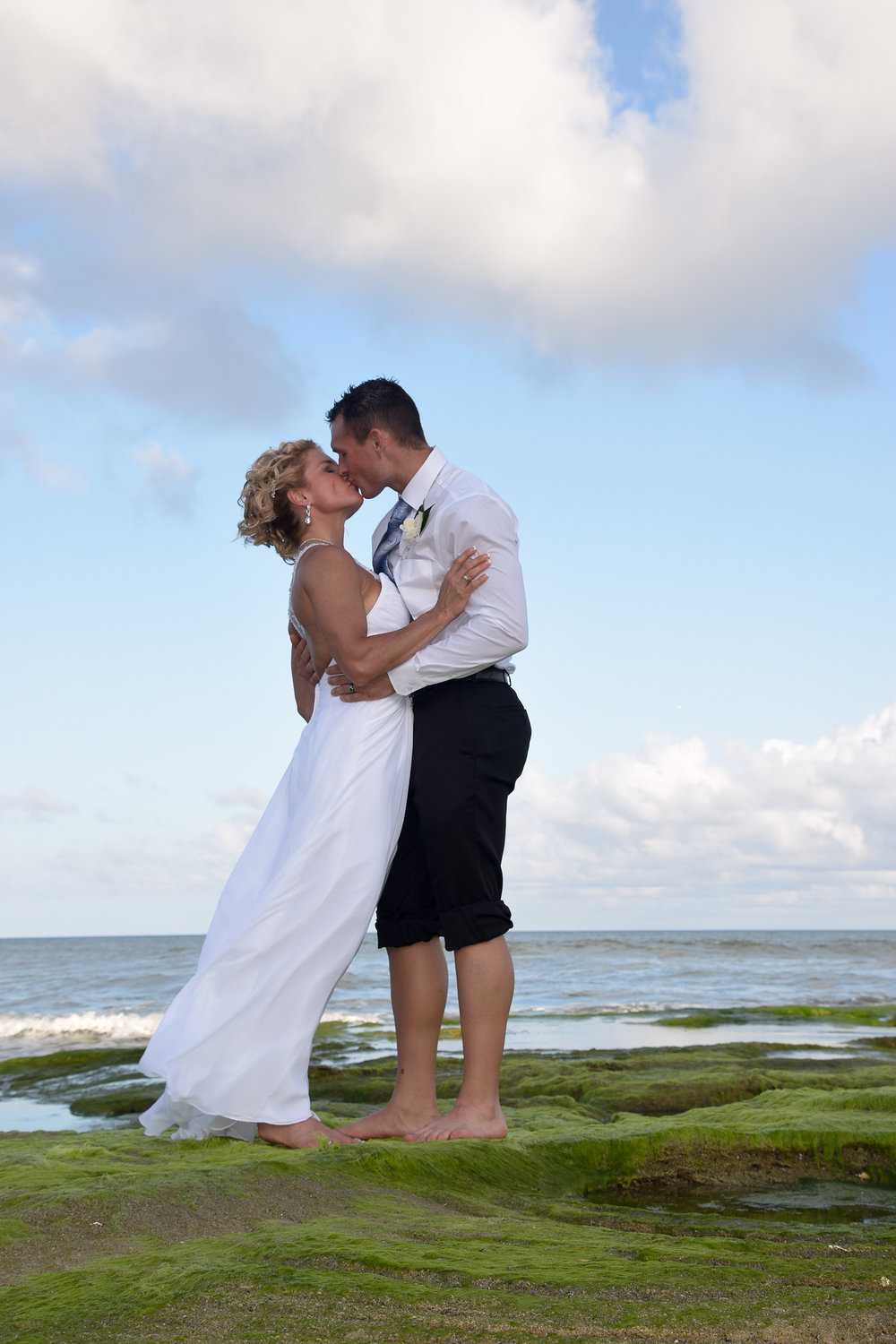 - Bride and groom sharing a kiss on the Coquina Rocks at low tide in Kure Beach, NC. Billy Beach Photography. Ocean in the background.
