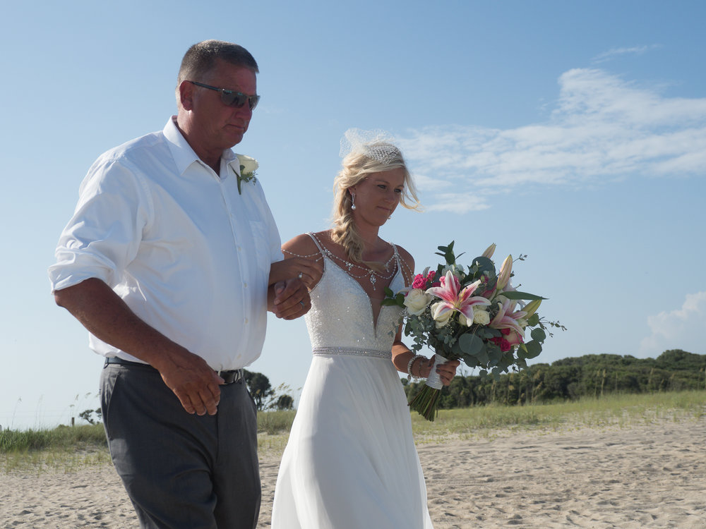 - Bride being walked across the sand on the way to her wedding ceremony at Fort Fisher, NC. Bride holding large bouquet. Billy Beach Photography.