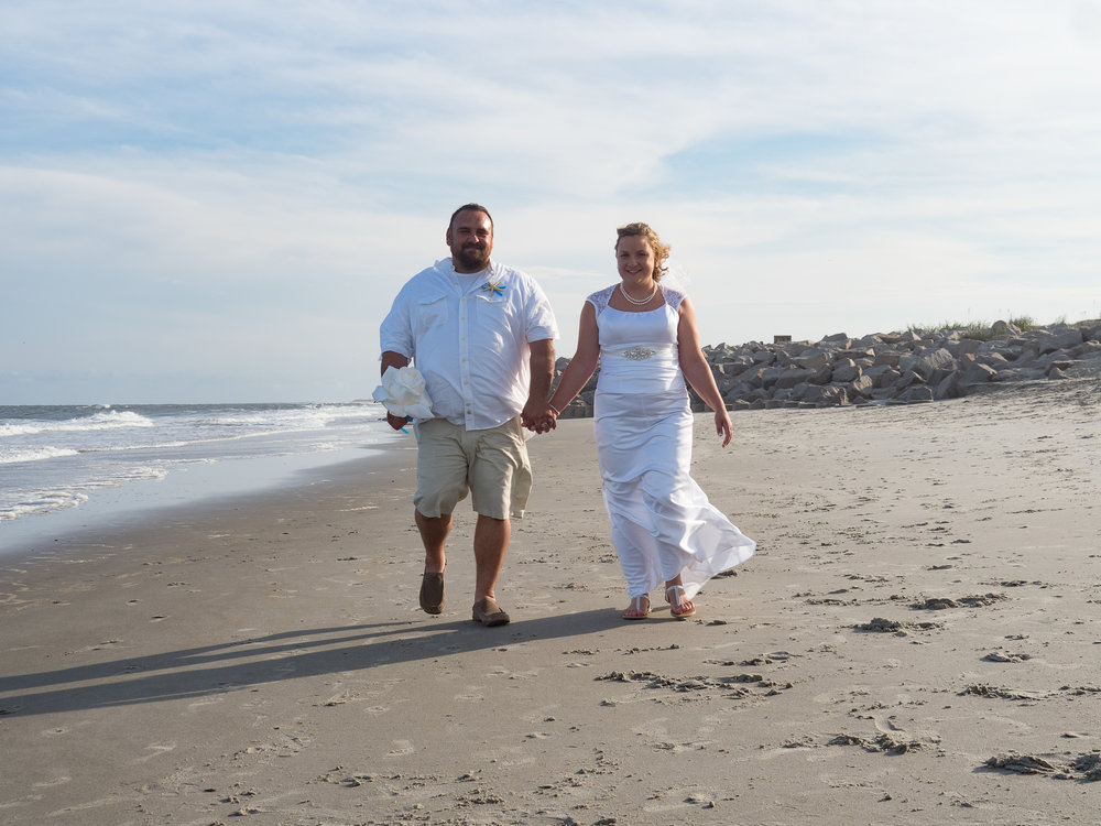 - Bride and groom walking on beach at Fort Fisher, NC. Groom holding bride's bouquet. Ocean and seawall in the background. Both are smiling. Billy Beach Photography.