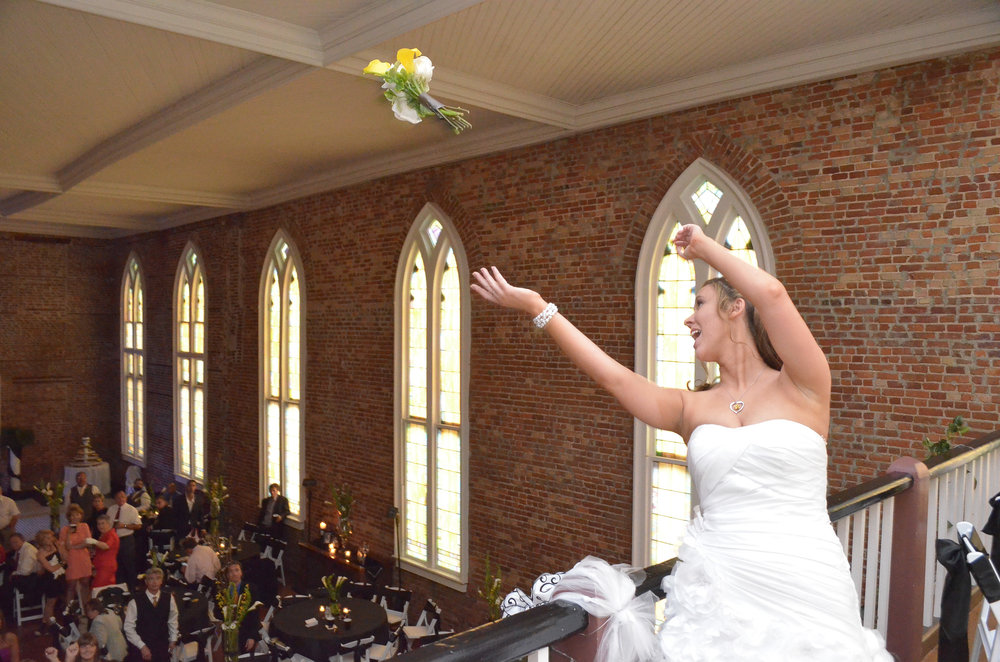 - Bride throws her bouquet from the balcony of Saint Thomas Preservation Hall in Wilmington, NC. Billy Beach Photography.