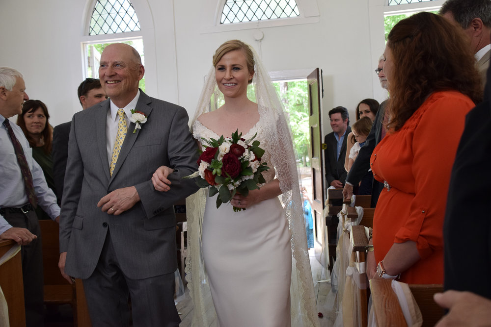 - Bride being escorted down the aisle by her father at the Lebanon Chapel in Airlie Gardens, Wilmington, NC. Billy Beach Photography.