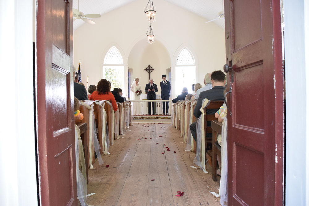 - Wedding Ceremony shot from the red doorway at the Lebanon Chapel in Airlie Gardens, in Wilmington, NC. Billy Beach Photography.