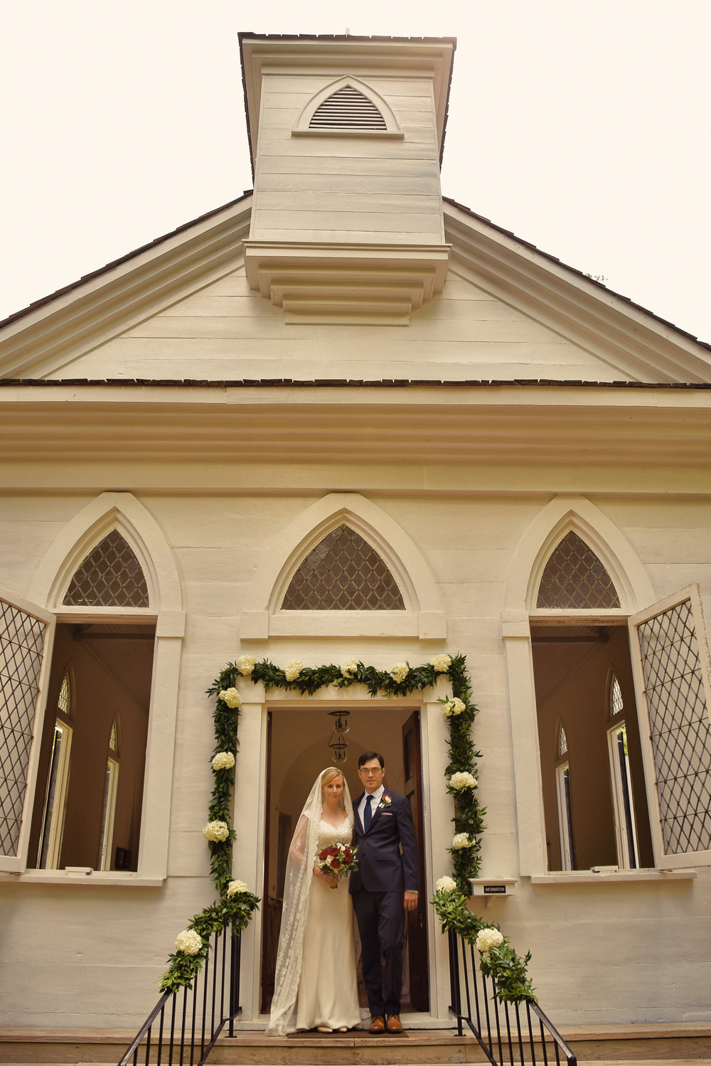 - Bride and groom posing for a photo outside the Lebanon Chapel in Airlie Gardens, Wilmington, NC. Billy Beach Photography.