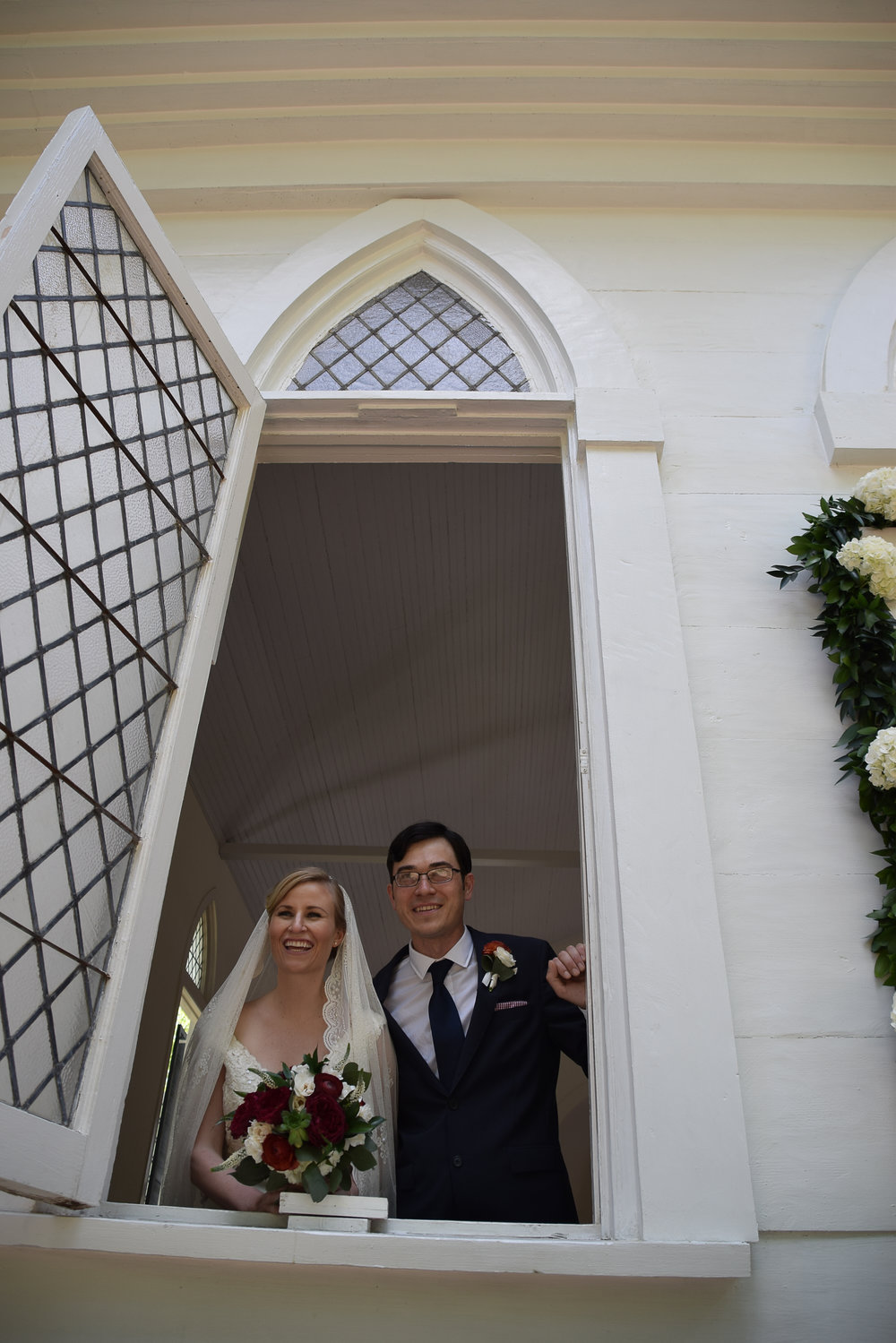 - Bride and groom looking out the Lebanon Chapel window in Airlie Gardens, Wilmington, NC. Candid moment. Billy Beach Photography.