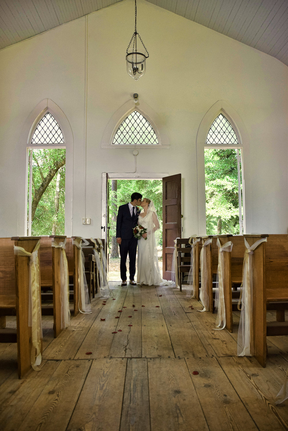 - Bride and groom sharing a kiss,at the doorway of the Lebanon Chapel in Airlie Gardens, Wilmington, NC. Billy Beach Photography.