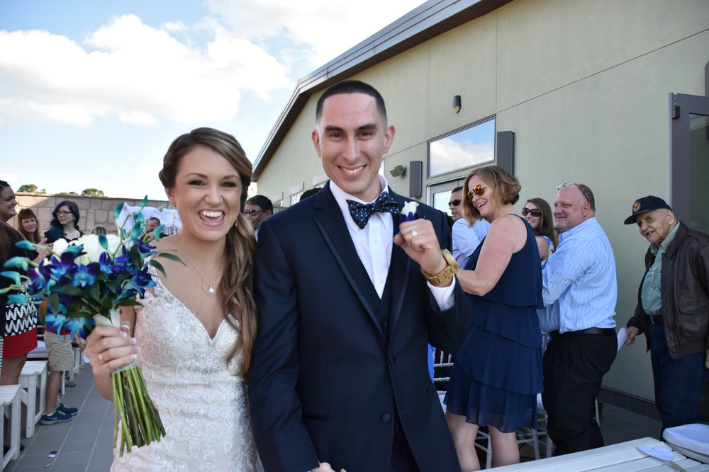 Joy. - Big smiles on Bride and Grooms face after wedding ceremony at Terraces on Sir Tyler in Wilmington, NC. Guests in the background.