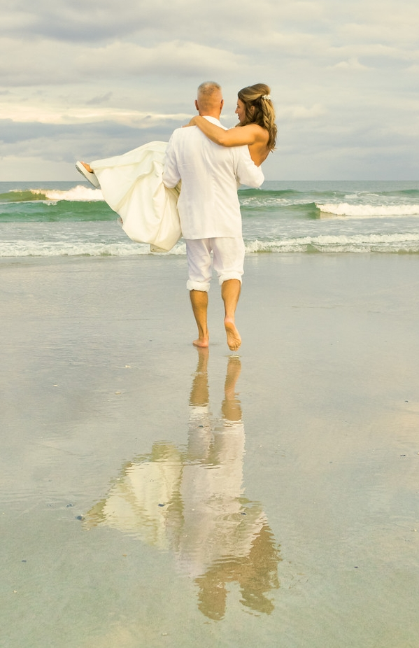- Groom carrying his bride to the surf on Topsail Beach, NC. Love the reflection. Billy Beach Photography.