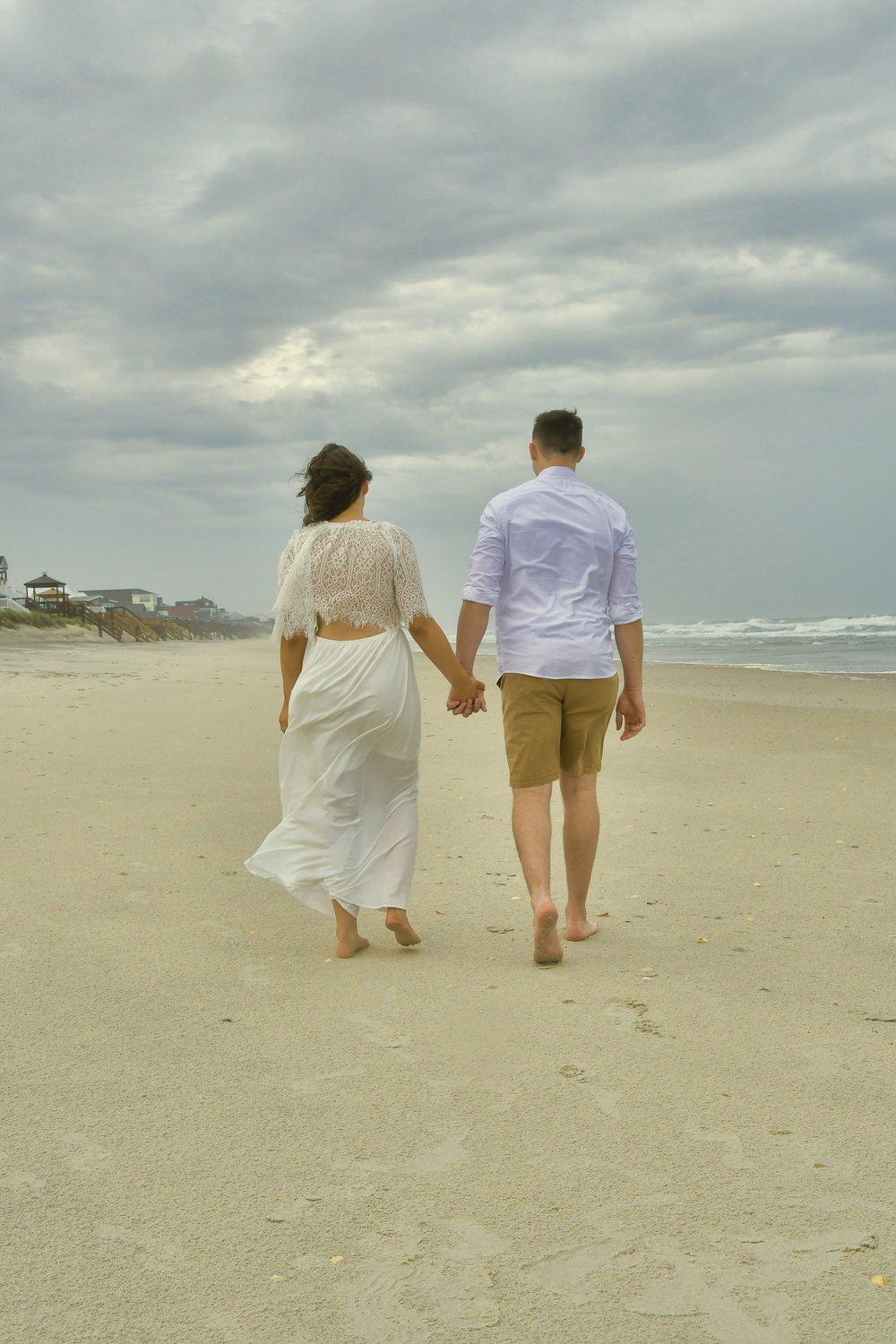 Walk - Bride and groom taking a walk on the beach after the ceremony. Surf City, Topsail Island, NC. Billy Beach Photography.