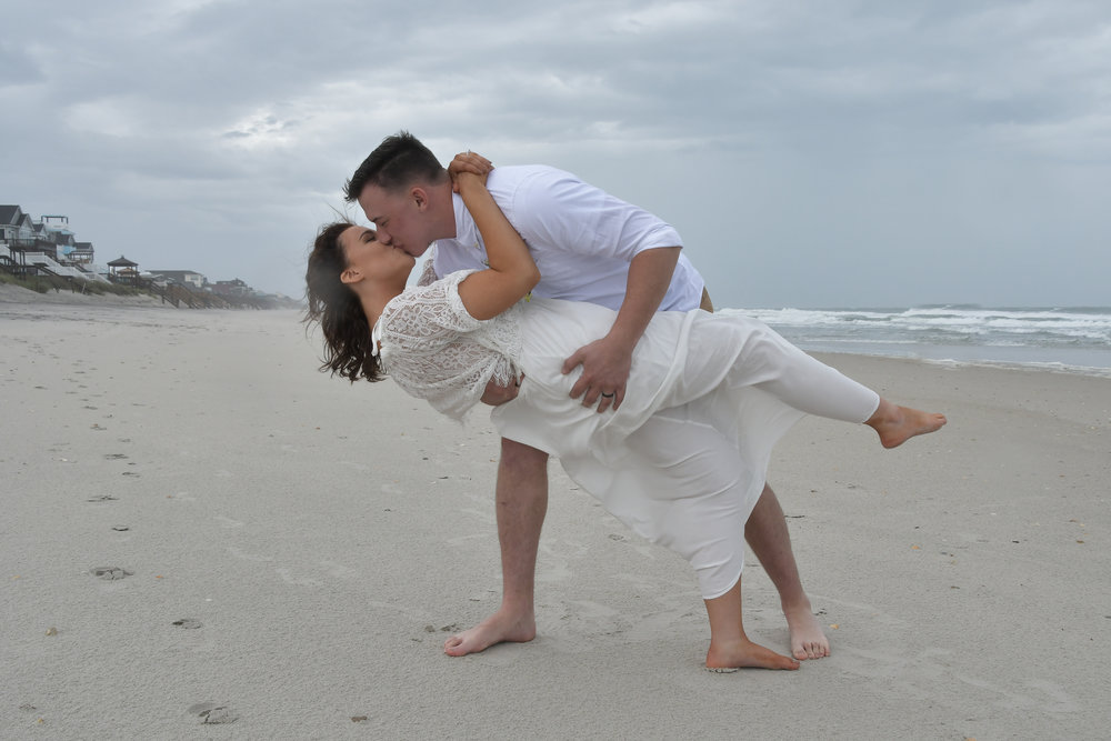 Dip - Groom dipping and kissing his bride in Surf City, Topsail Island, NC. Billy Beach Photography.