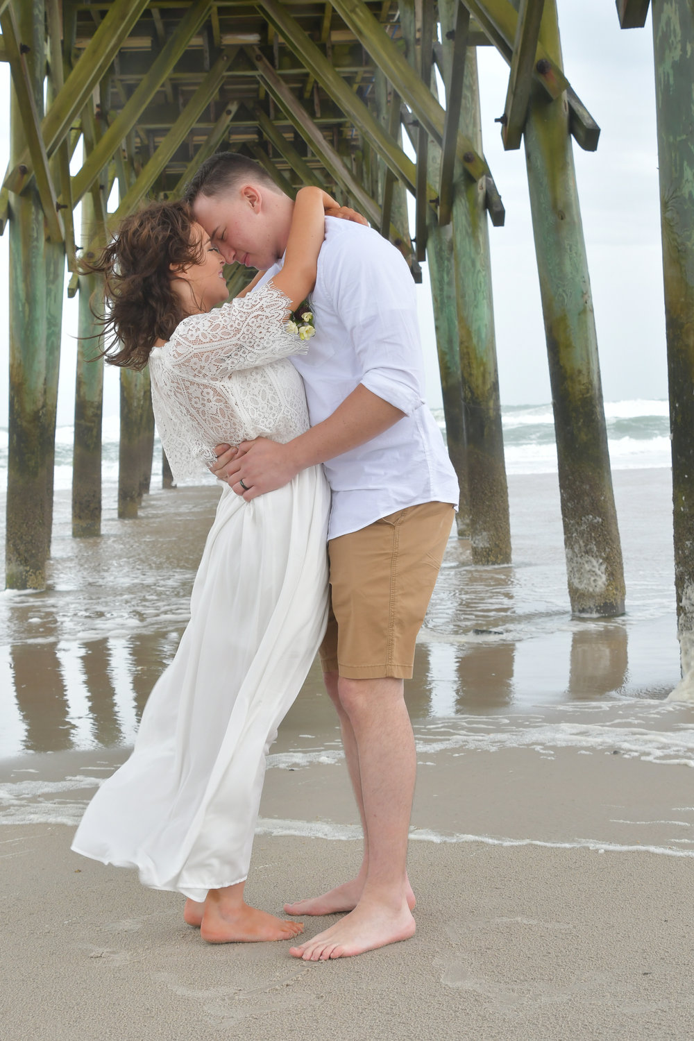 Pier - Bride and groom share a moment under the Surf City Pier, on Topsail Island, NC. Billy Beach Photography.
