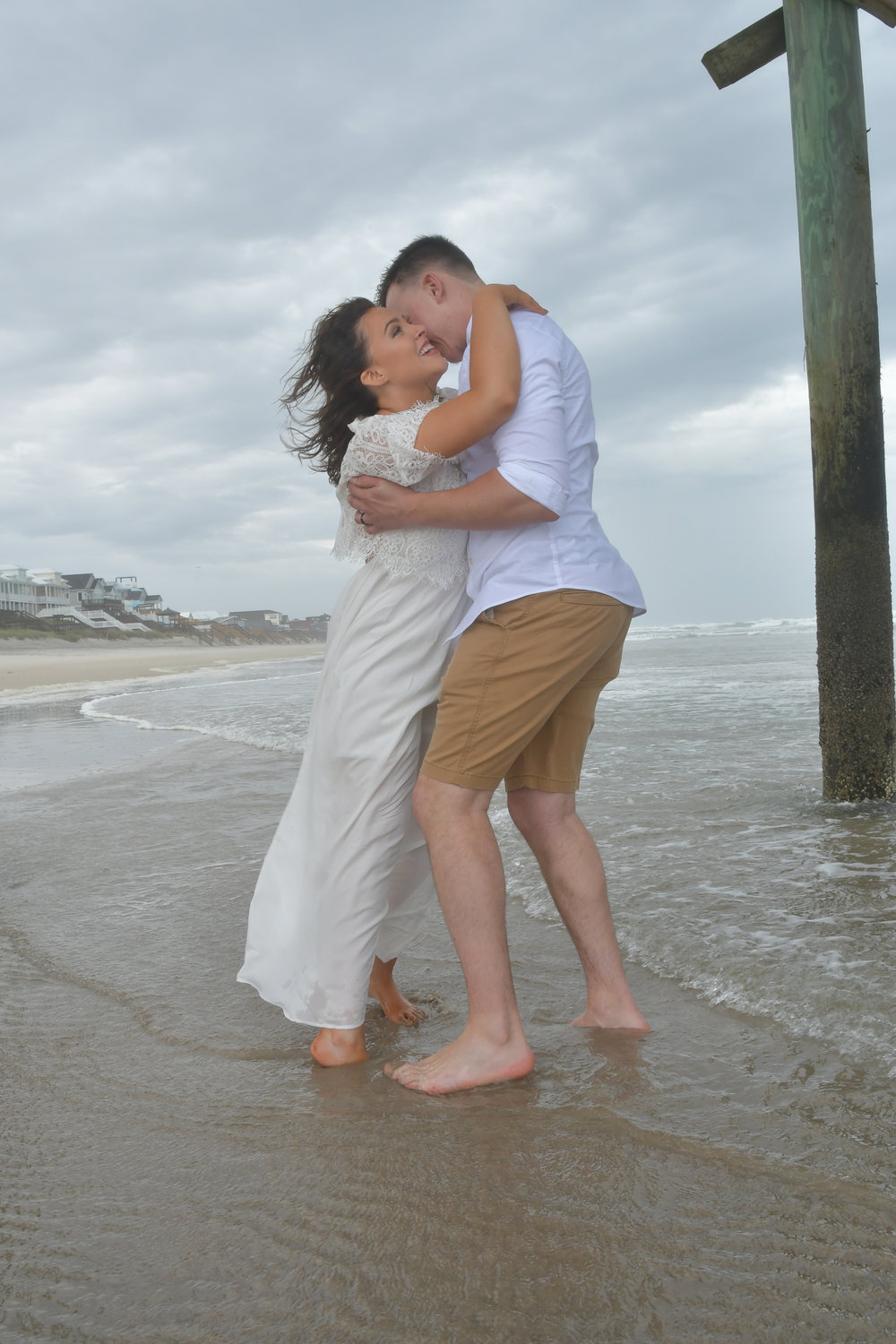 Passion - Despite the wind and the light rain, bride and groom share a moment near the Surf City Pier in Surf City, Topsail Island, NC. Billy Beach Photography.