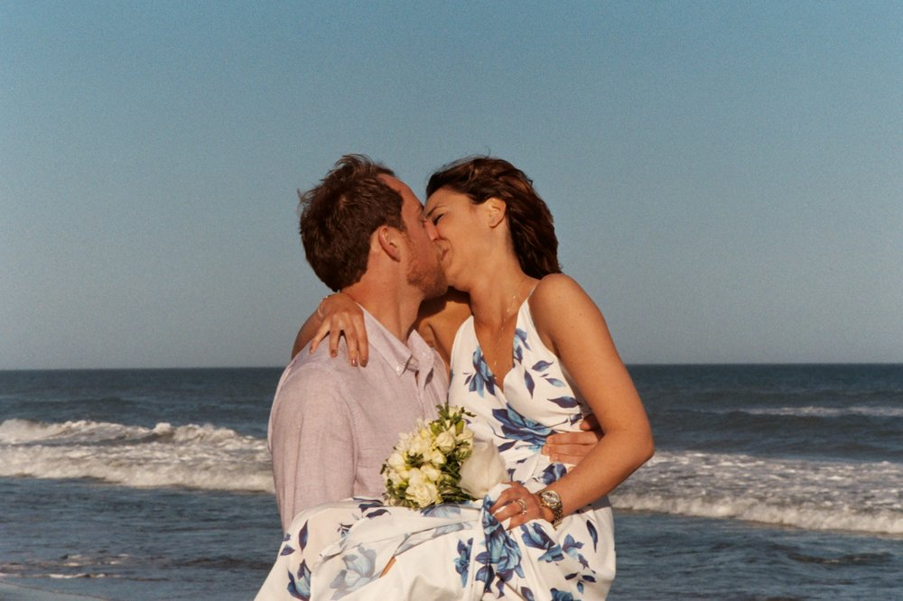 - Kiss on the beach with ocean in the background. Shot on film. Kodak Color Plus 200.