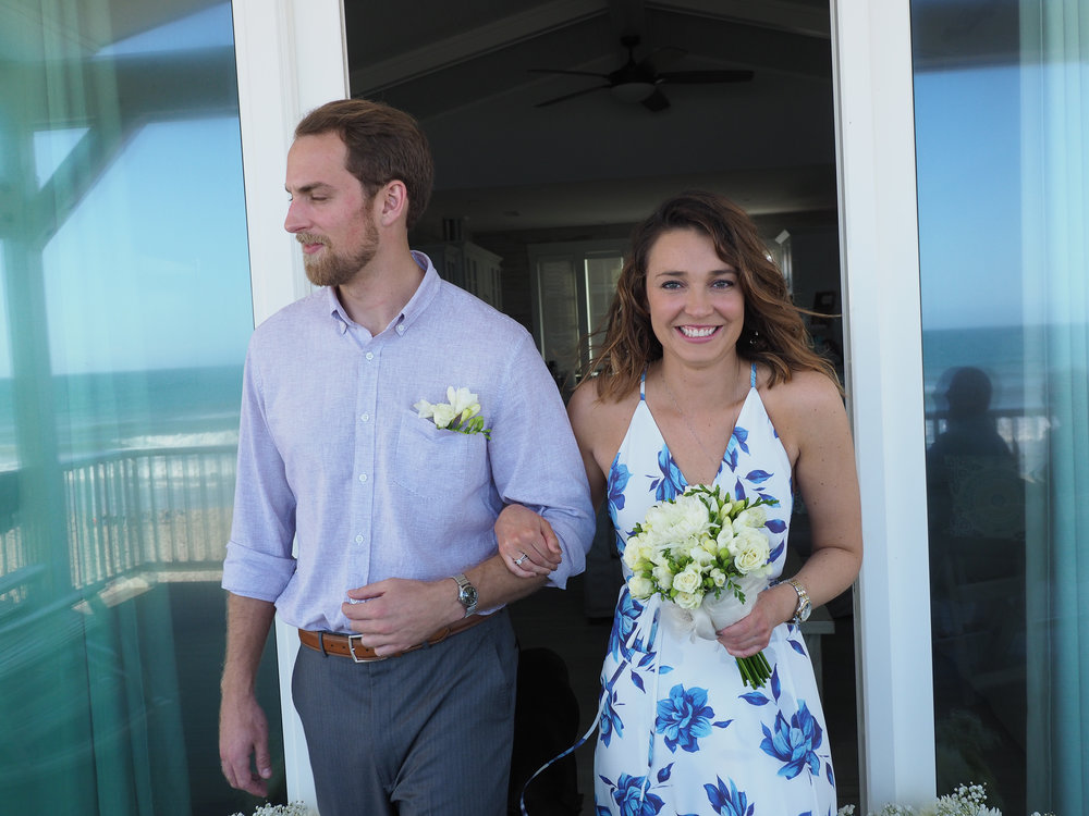 - Bride and Groom walking to the deck for their wedding ceremony. Wrightsville Beach, NC. Billy Beach Photography.
