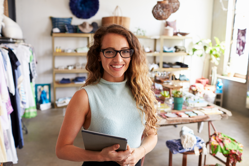 woman-in-retail-shop-learning-to-sell-online-with-ipad-and-feeling-happy.jpg