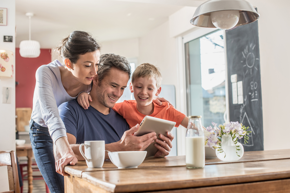 Family-in-kitchen-on-tablet-happy-learning-online-business.jpg